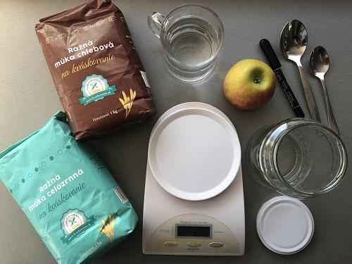 K založeniu materského kvásku potrebujeme: ražnú celozrnnú múku, ražnú chlebovú múku, jablko, fixku, 2 lyžice, zaváraninový pohár, vodu